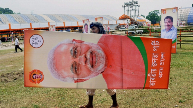 A worker carries a poster of Prime Minister Narendra Modi ahead of the NDA governments third anniversary celebrations on May 26 in Guwahati on Wednesday