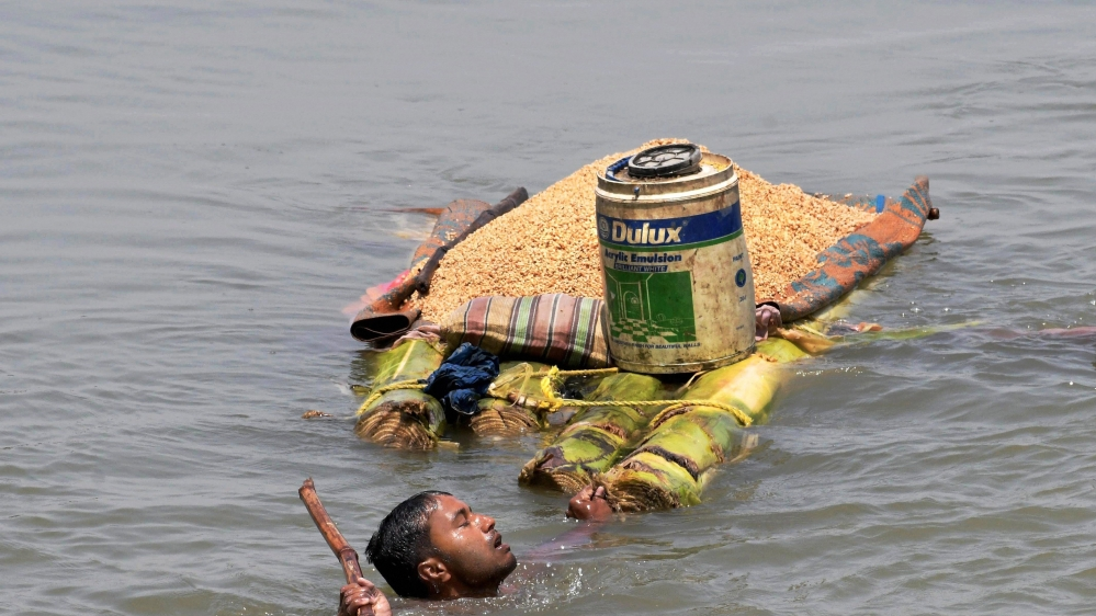 A man carries grains on a banana raft as he moves to a safer location from a flooded village in Araria district of Bihar