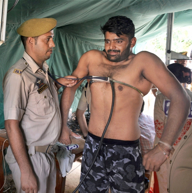 A candidate goes through checks during a Jammu and Kashmir Police recruitment drive for  posts of sub-inspectors at Gulshan Ground in Jammu.