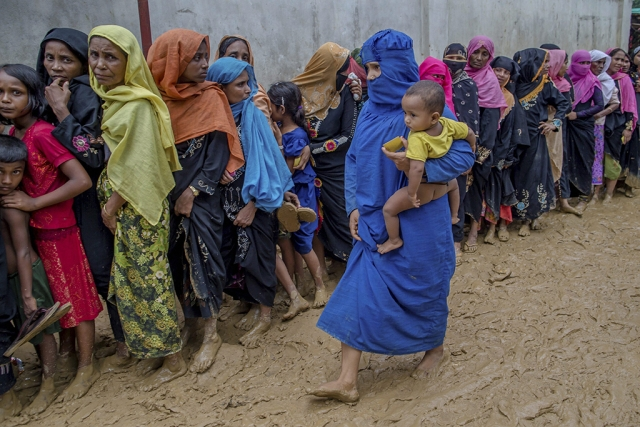 Newly arrived Rohingya women wait for their turn to collect building material for their shelters distributed by aid agencies in Kutupalong refugee camp, Bangladesh.