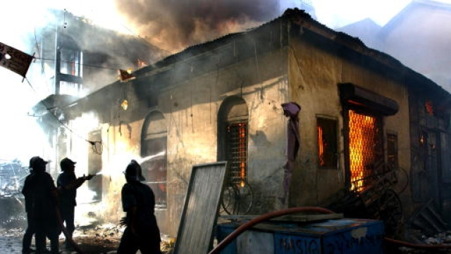 A file photo of firemen attempting to put out a rapidly spreading fire in a Muslim neighborhood of central Ahmadabad in March 2002