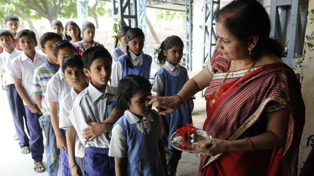 File photo of a government school in Bhopal where a teacher is welcoming students with a tilak