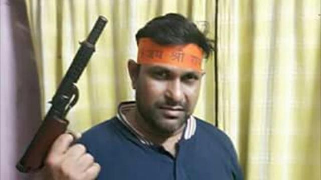 Santosh Kumar seen brandishing a weapon.