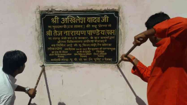 BJP workers dismantling the plaque on the wall of a hospital which was inaugurated by Akhilesh Yadav