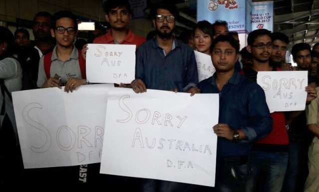 """People stand with placards reading """"Sorry Australia"""" at Lokpriya Gopinath Bordoloi International Airport in Guwahati after a stone was thrown at their bus."""