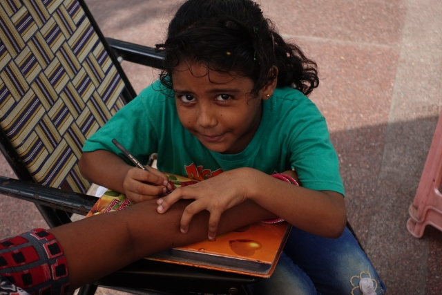 A child learning skill putting  henna on hand  from here mother on international child day in New Delhi