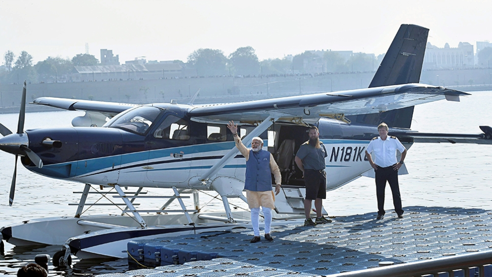 Prime Minister Narendra Modi waves to the crowd as he boards a seaplane on the Sabarmati river front in Ahmedabad on Tuesday