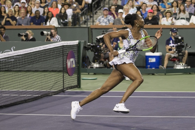 Venus Williams chases down a shot from opponent and sister Serena Williams during the third round of the BNP Paribas Open tennis tournament at the Indian Wells Tennis Garden in Indian Wells, Calif.