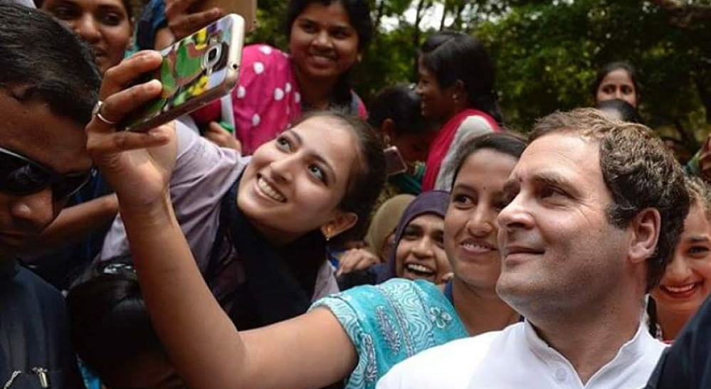 Congress President Rahul Gandhi poses for a selfie with students during his visit to Maharani College in Mysuru.