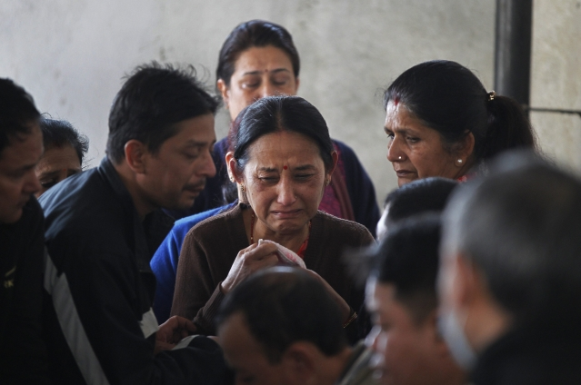 Unidentified family members of a passenger of a Bangladesh's US-Bangla Flight BS211mourn as they wait to receive the body at the government hospital in Kathmandu, Nepal.