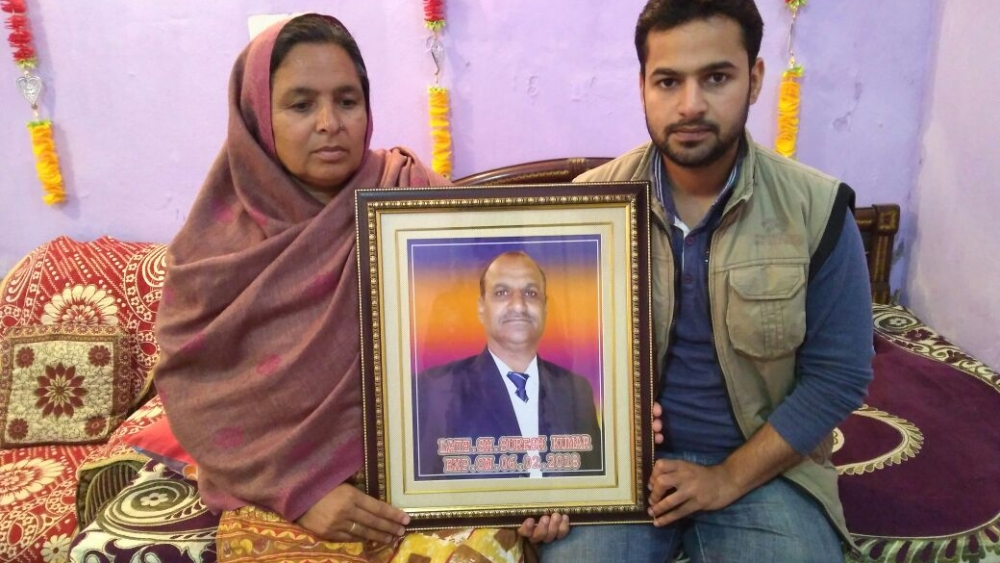 Puneet Choudhary (right) and his mother Anita Choudhary hold the portrait of Suresh Kumar Choudhary, at their home in Ramgarh sector of Jammu and Kashmir