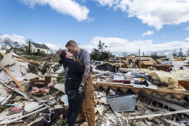 Mia Polaski and her husband Ryan Polaski kiss during a brief moment of respite while clearing debris from her father Randy's storm damage home, in Elon, Virginia. Virginia's governor has declared a state of emergency after storms ripped through parts of western Virginia.