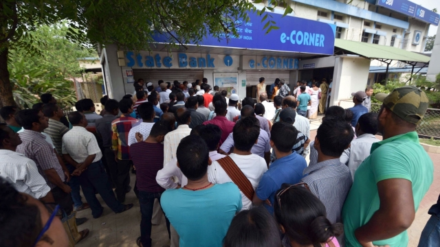 People wait outside an ATM, in Assam's Nagaon district. Currency shortage was reported in Andhra Pradesh, Telangana and Madhya Pradesh in the past few weeks. There were also complaints of shortage in parts of Maharashtra, Gujarat and Bihar