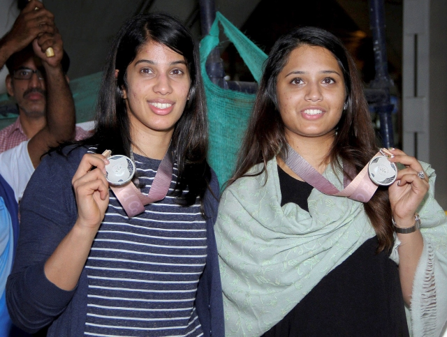 Squash players Joshna Chinappa and Dipika Pallikal Karthik display their Commonwealth medals on arrival at Chennai airport