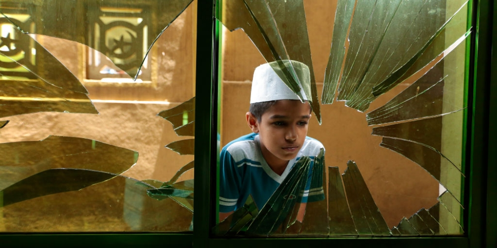 A Sri Lankan Muslim boy looks through a broken glass window among the debris of a vandalised mosque in Digana, Kandy in Sri Lanka on March 9, 2018