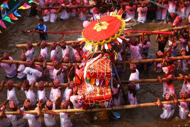 Nepalese people carry chariots on their shoulders in celebration of the Bisket Jatra festival in Tokha of Kathmandu, Nepal. The festival is celebrated with chariot processions of various gods and goddesses to welcome the Nepalese New Year and the beginning of spring in Nepal.