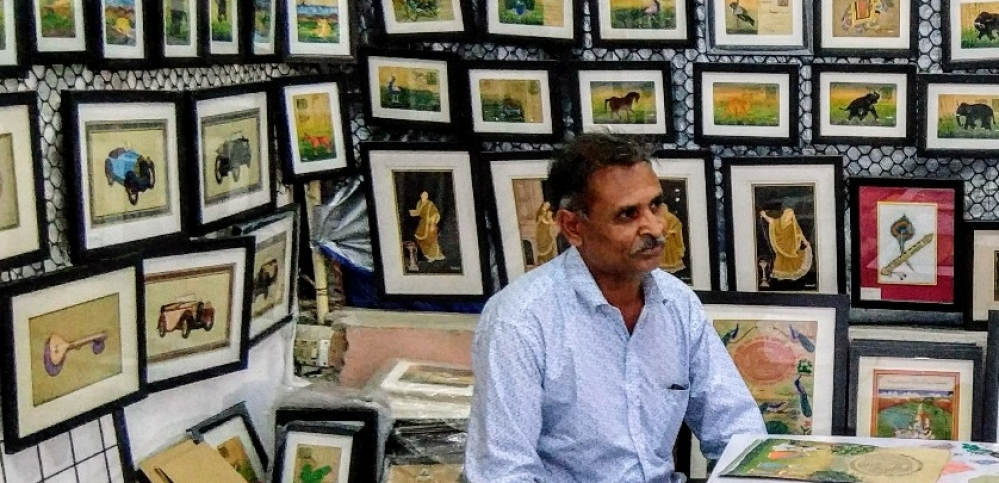 Artist Panchu Lal Raw with his paintings