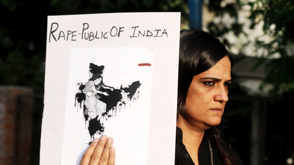 A woman holds a placard at a protest march in Gurugram, Haryana against the brutal rape of a minor in Kathua, Jammu and Kashmir