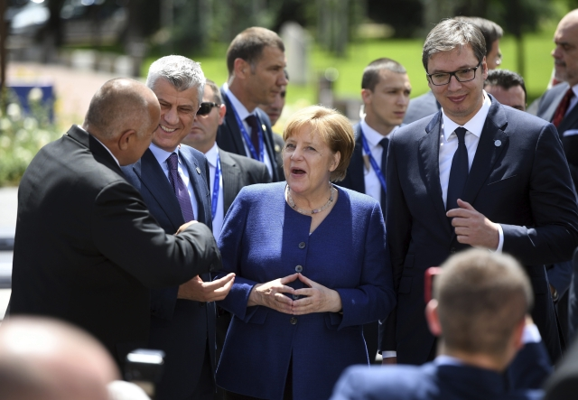 German Chancellor Angela Merkel, centre , speaks with Serbia President Aleksander Vusic, right, Kosovo's President Hashim Thaci, second left, and Bulgarian Prime Minister Boyko Borissov, left, during a group photo at an EU and Western Balkan heads of state summit at the National Palace of Culture in Sofia, Bulgaria