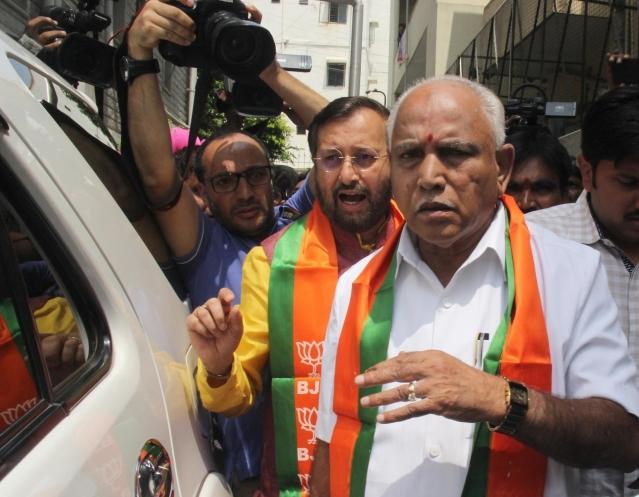 BJP leaders B.S. Yeddyurappa and Prakash Javadekar arrive after meeting Karnataka Governor Vajubhai Vala in Bengaluru.