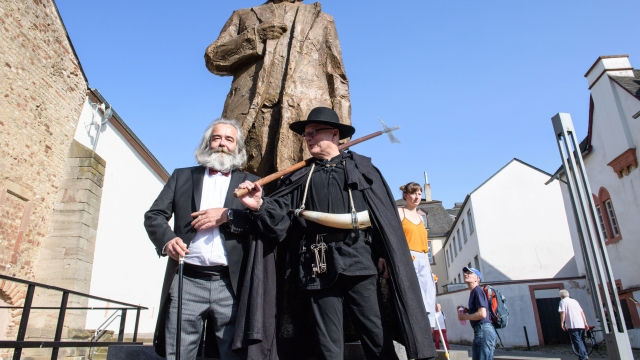 Heinrich Laufer (L) dressed as revolutionary Karl Marx poses for pictures in front of the Karl Marx statue gifted by China and installed at Trier ( Germany) where Marx was born.