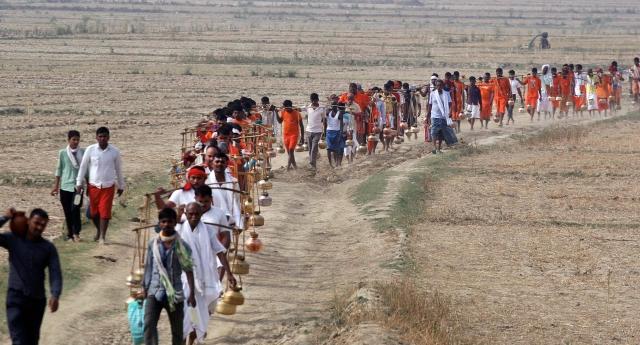 Hindu devotees (Kanwariyas) carry holy water of river Ganga to perform 'abhishek' at Padilla Mahadev temple, on the 1st day of Purshottam (Adhimas) of Hindu calendar, in Allahabad.