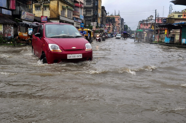 A car wades through a flooded street after heavy downpour in Silchar, Assam.