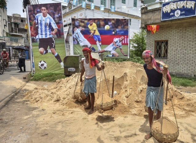 Labourers busy in work in front of posters of Soccer stars as the FIFA World Cup 2018 fever has gripped the locality, in Howrah district of West Bengal.