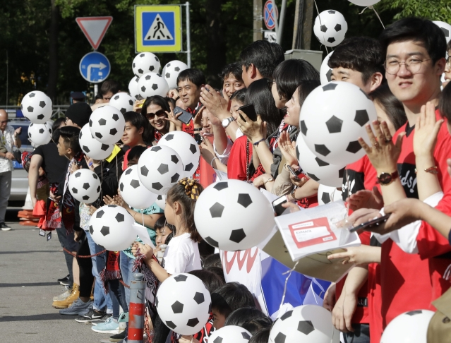 South Korean soccer fans hold soccer ball-shaped balloons upon South Korea's national soccer team's arrival at the team hotel for the 2018 soccer World Cup in St Petersburg, Russia.