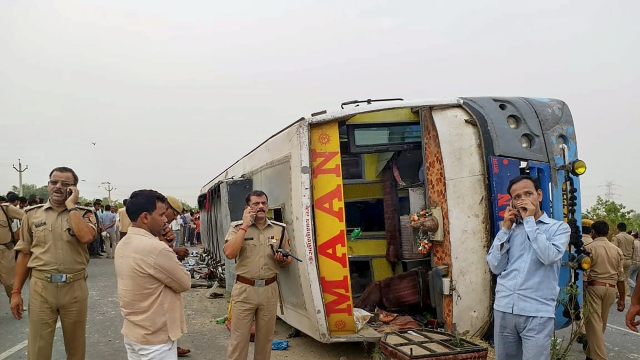 Police personnel conduct investigation at the site where a speeding bus overturned after hitting a road-divider in Mainpuri, Uttar Pradesh
