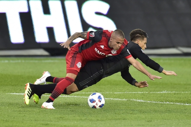 Toronto FC defender Auro, left, takes down D.C. United midfielder Yamil Asad and picks up a yellow card on the play during the first half of an MLS soccer match, in Toronto.