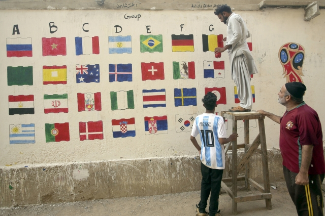 Pakistani football fans paint flags of participating countries in the upcoming FIFA 2018 World Cup, in suburbs of Karachi, Pakistan.