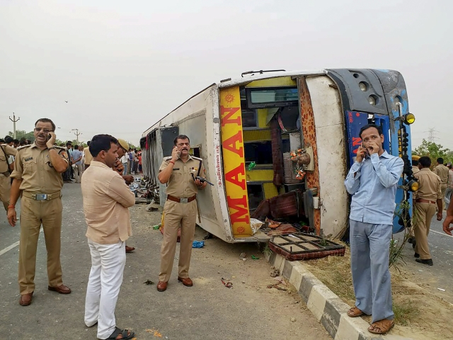 Police personnel conduct investigation at the site where an allegedly speeding bus overturned after hitting a road divider,  17 passengers were killed and 20 were injured in the accident in Mainpuri.