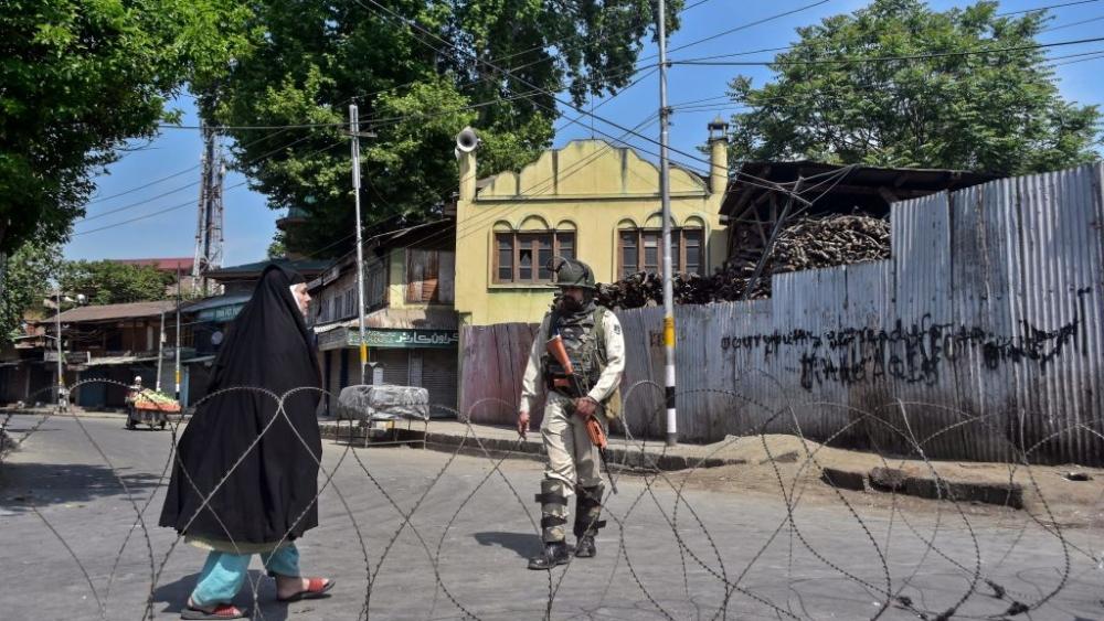 A Kashmiri woman walks past Indian paramilitary trooper standing guard in Srinagar
