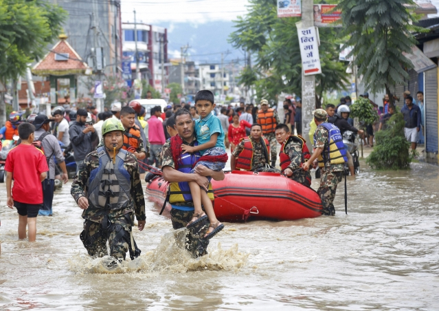 Nepalese army men rescue a sick boy from a flooded area in Bhaktapur, Nepal. The flooding was caused by overflowing of the Hanumante River following heavy rain.