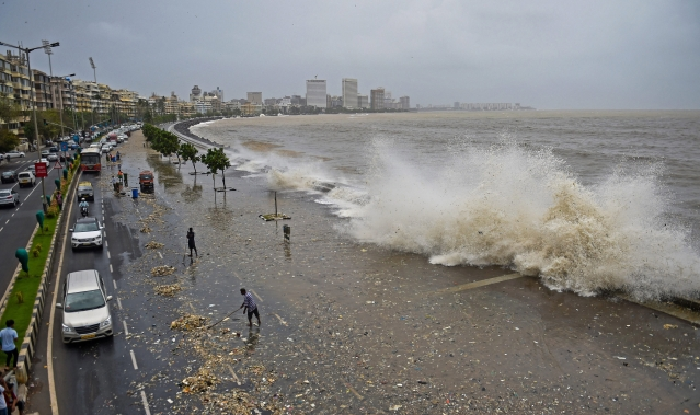 Brihanmumbai Municipal Corporation (BMC) workers clear the garbage washed ashore during high tide on a road along the Marine Drive in Mumbai.