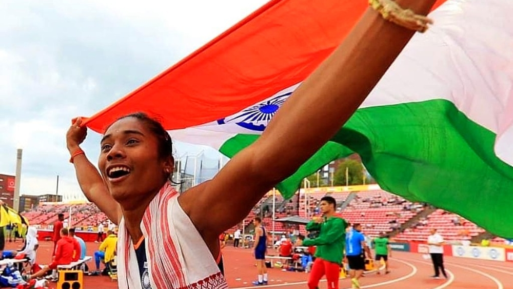 Hima Das celebrates with the national flag after winning the first-ever athletic gold for India at a world event