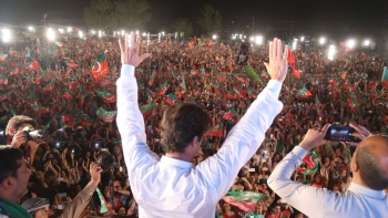 PTI's Imran Khan, a frontrunner for Pakistan's premiership in the July 25 vote, waving to his supporters at an election rally on Monday