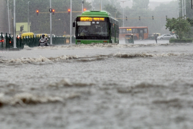 Traffic wades through water logged roads at  ITO, due to heavy rain in New Delhi.