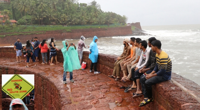 """A visitor poses for selfies despite of a board stating""""Danger, No Selfie Zone"""" put up at Aguada fort in Goa's Sinquerim. Amid a spate of drownings and accidents along Goa's coastline, the state's popular beaches and tourist spots have set up """"no selfie"""" zones."""