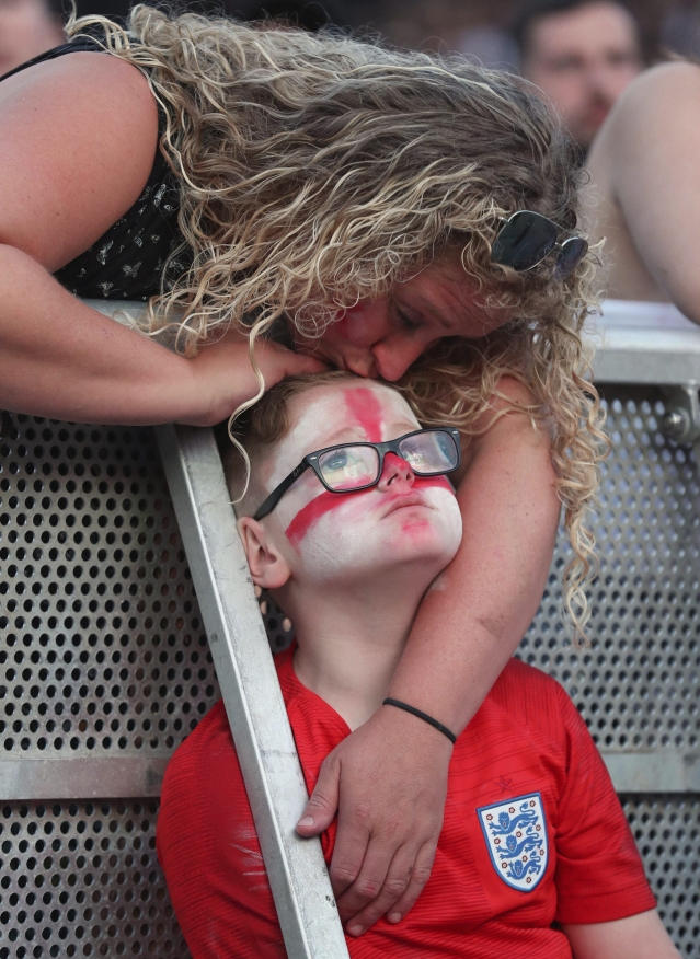A young fan is consoled as he watches the 2018 World Cup semi final soccer match between Croatia and England in Russia, at the Castlefield Bowl in Manchester, England.