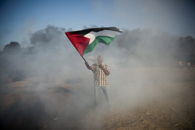 A Palestinian protester wears a plastic bag on his head as a protection from teargas, waves a national flag during a protest at the Gaza Strip's border with Israel. Violence erupted at the Gaza border.