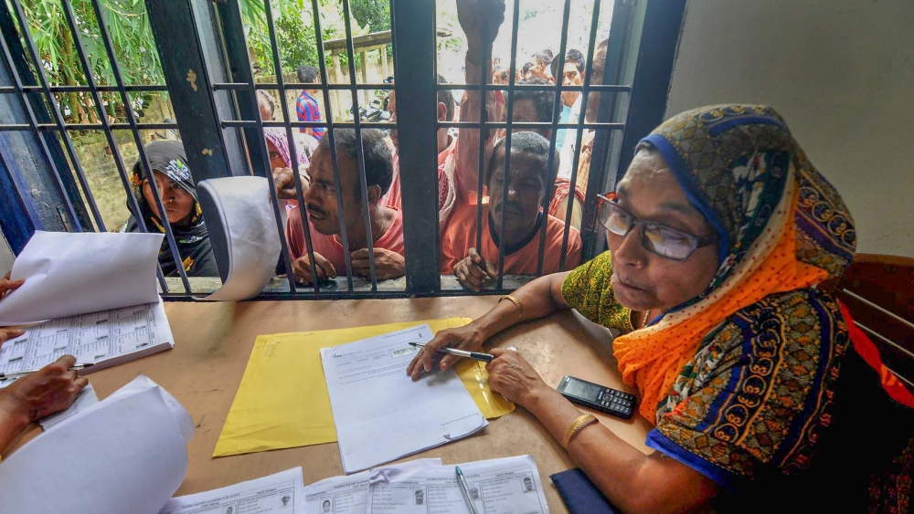 People wait in a queue to check their names on the final draft of the state's National Register of Citizens after it was released, at an NRC Seva Kendra, in Morigaon