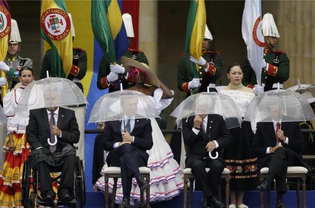 Ecuador's President Lenin Moreno, from left, Argentina's President Mauricio Macri, Chile's President Sebastian Pinera and Mexico's President Enrique Pena Nieto hold umbrellas during the presidential inauguration ceremony for Ivan Duque, in Bogota, Colombia.