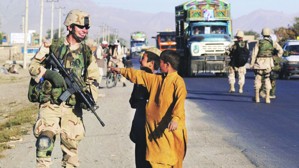 An American troop shares a light moment with two Afghan kids