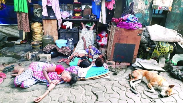 A family and a street dog sleep on a footpath in Kolkata