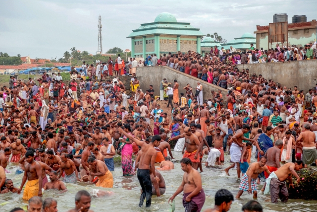 "Devotees take bath and perform rituals at the famous Kanyakumari beach on the occasion of ""Aadi Amavasai"", in Kanyakumari district."