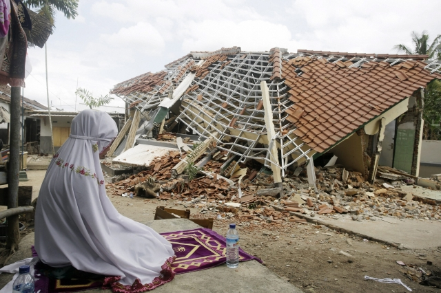 A woman performs a prayer in front of debris from Sunday's earthquake in West Lombok, Indonesia. Scientist say the powerful Indonesia earthquake that killed more than 300 people lifted the island it struck by as much as 25 centimeters.