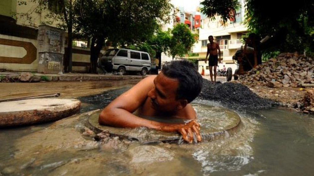 A manual scavenger cleans a sewer, without any safety gear or protective equipment. Representative image