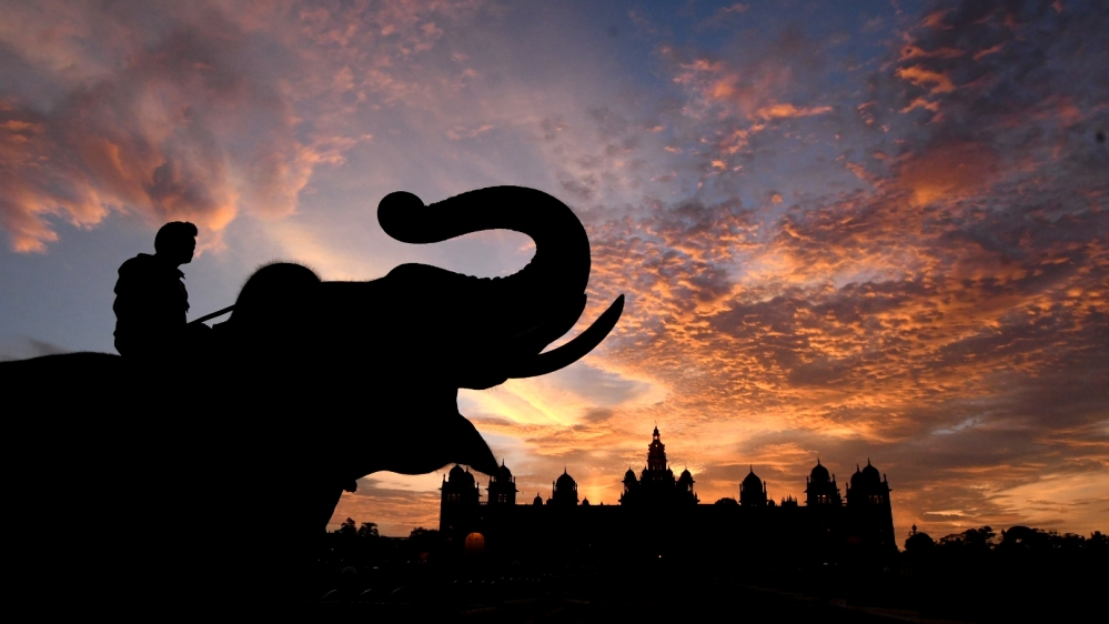 A silhouette of Dasara elephants outside the Mysore Palace in the backdrop of orange-tinged skies during sunset, in Mysuru.